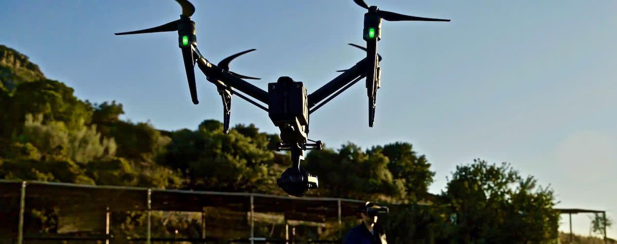 vista trasera del drone dji inspire 2 volando y al fondo piloto de drones con gafas rodeado de arboles