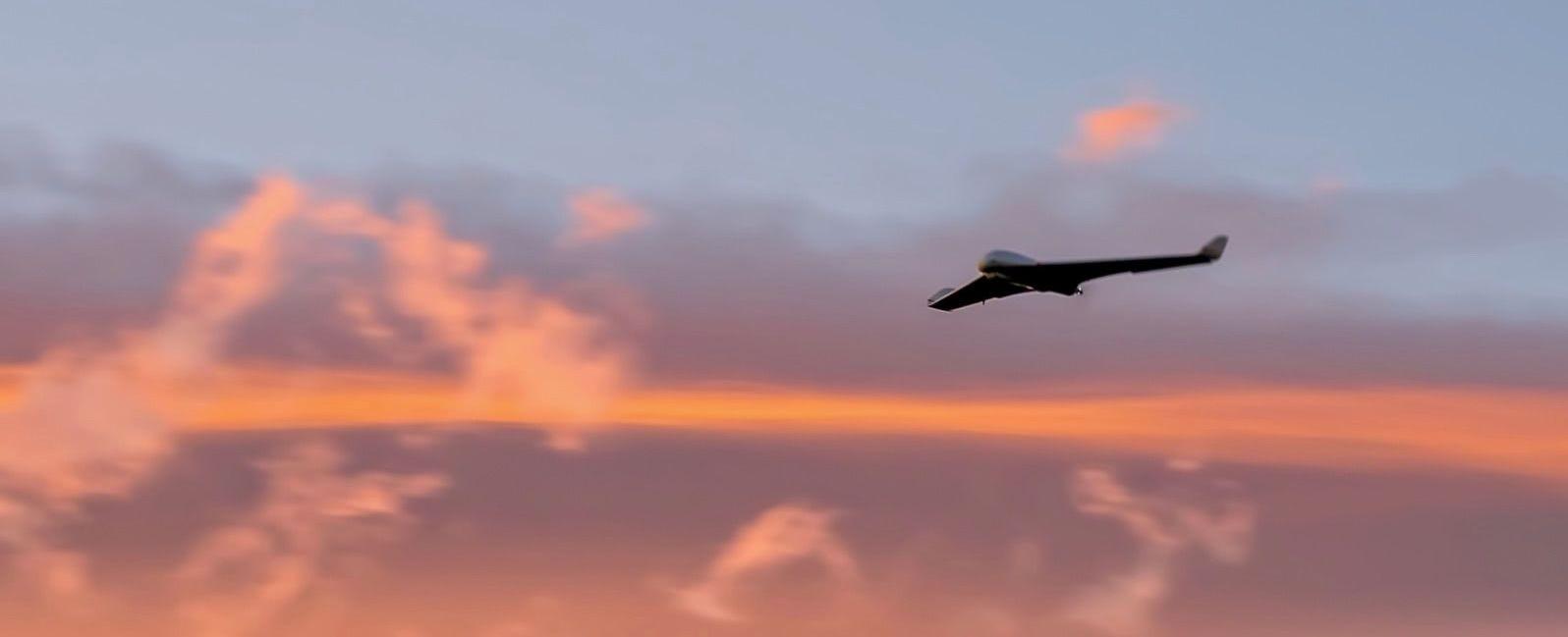 drone de ala fija volando al atardecer con un cielo de color naranja al fondo