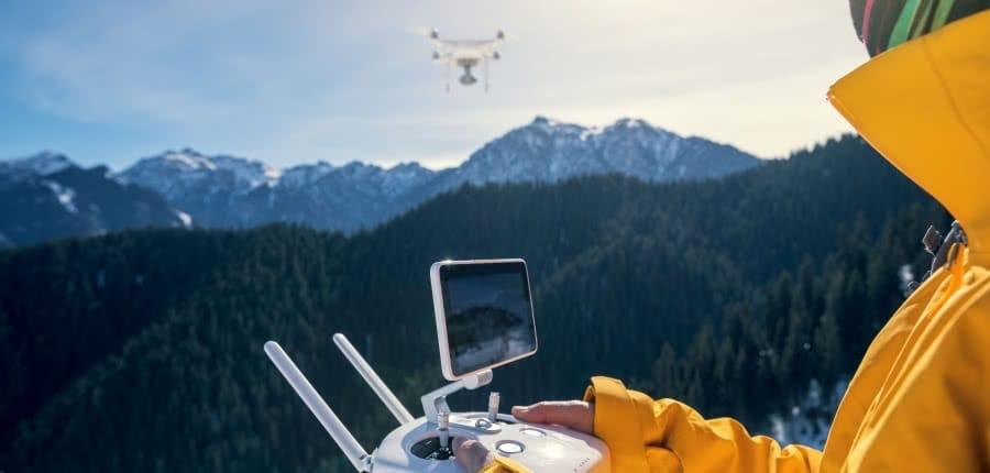piloto de dron con chaqueta amarilla volando dron en la nieve