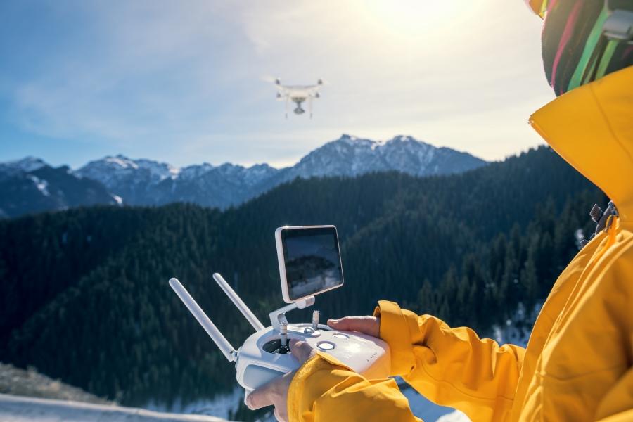 piloto de dron volando en la nieve