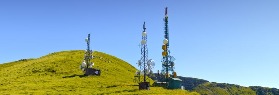 torretas de telecomunicaciones en pradera verde con cielo azul