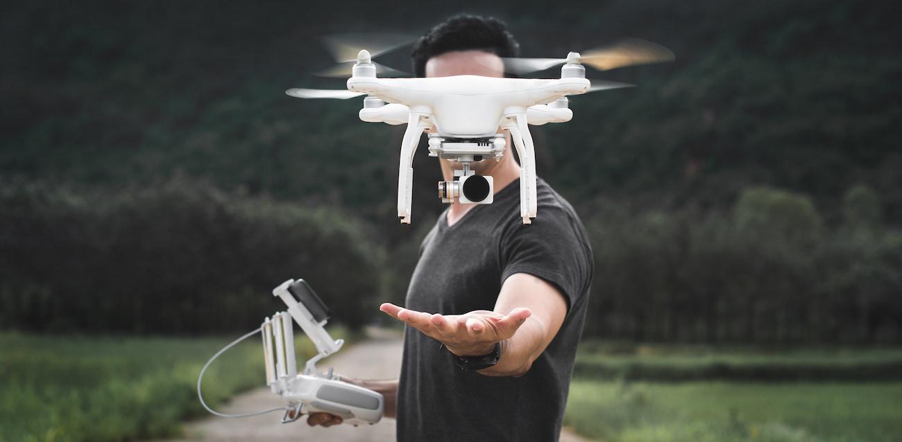 hombre vestido de negro con brazo extendido bajo dron dji phantom y emisora en la otra mano, con fondo de bosque oscuro
