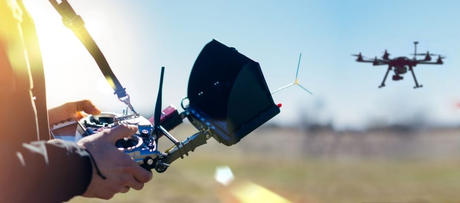 detalle de manos sujetando emisora de dron con dron volando al fondo