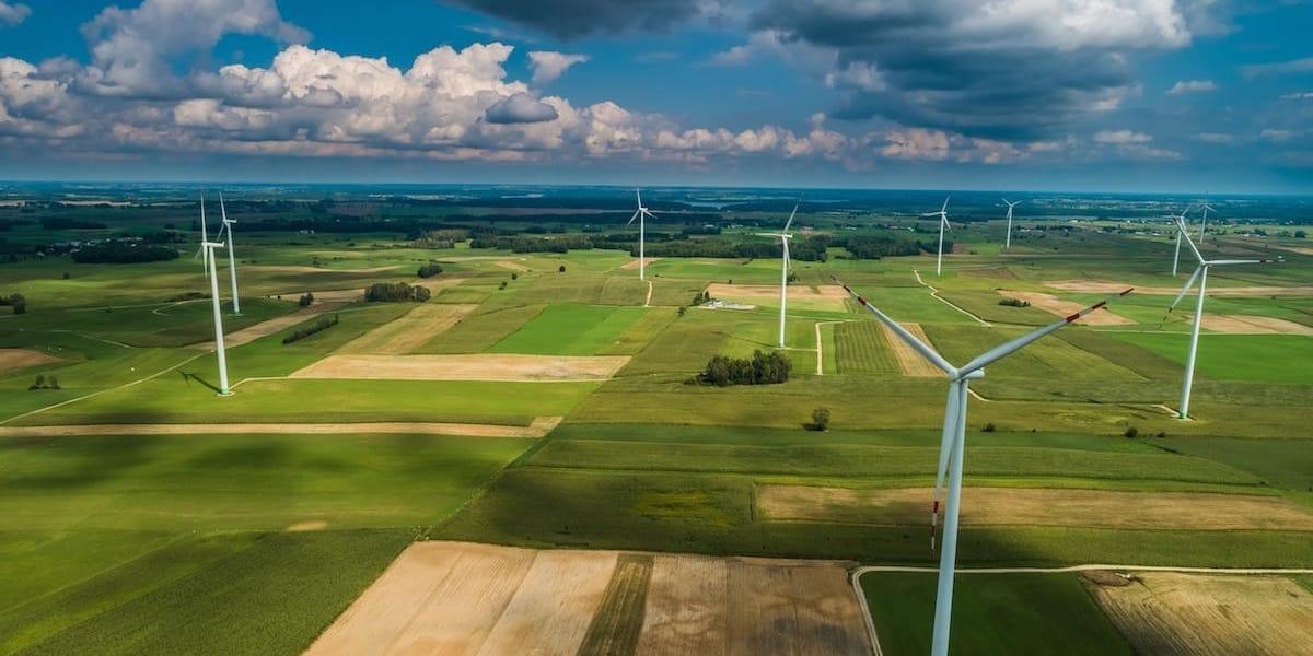 vista aerea de molinos de vientos siendo inspeccionados por dron
